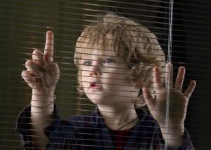 Een kind die voor het glazen raam staat